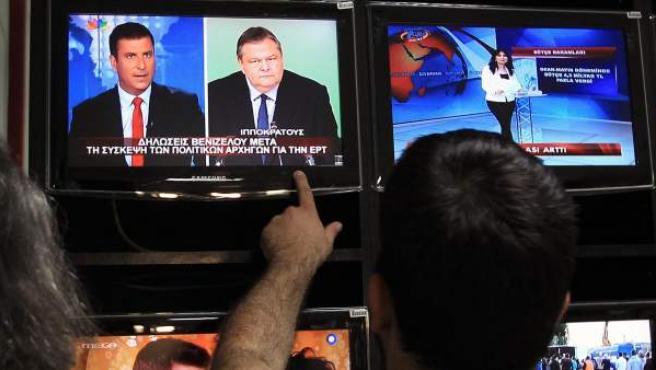 Empleados del canal estatal de televisión y radio ERT observan en televisión declaraciones del líder del partido PASOK, Evangelos Venizelos.