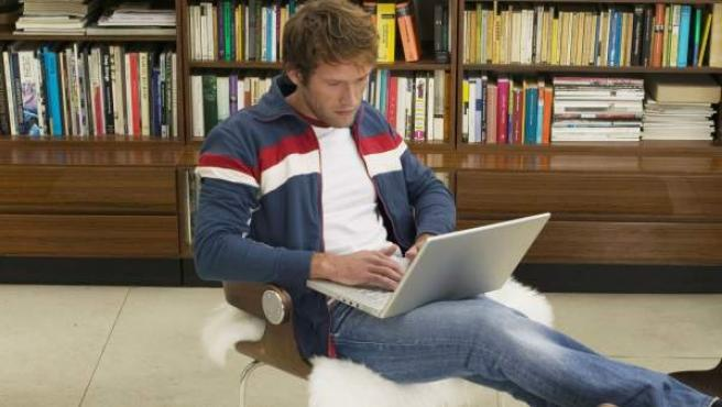 Un hombre trabajando en su casa con un portátil.