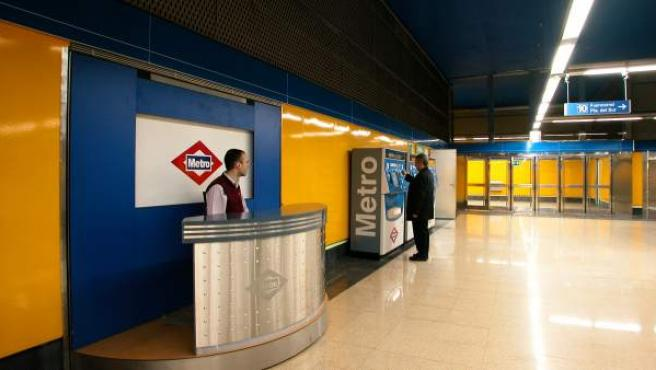Un empleado de estación de Metro observa cómo un cliente saca un billete en una máquina automática.