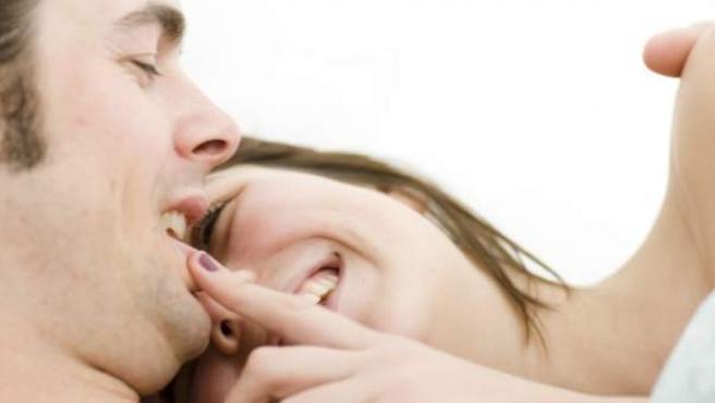 Una pareja se sonríe en la cama.