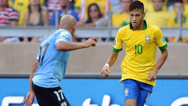 Neymar conduce el balón ante la presión de Arévalo durante la semifinal de la Copa Confederaciones entre Brasil y Uruguay.