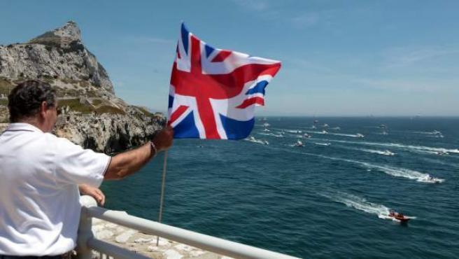 Un hombre sostiene una bandera británica en Gibraltar.