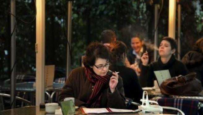 Varias personas fuman en una terraza de un bar.