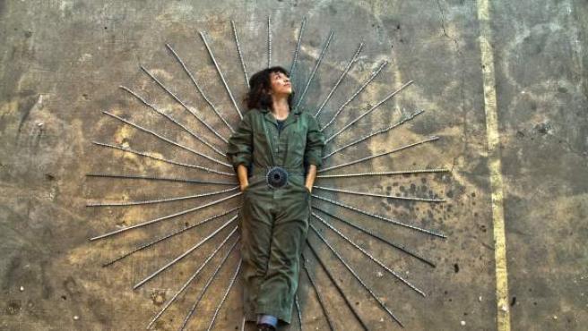 La artista mitad mexicana mitad brasileña Carolina Fontoura posa junto a cadenas de bicis, con las que realiza lámparas.