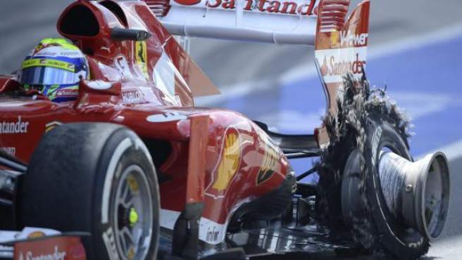 Felipe Massa entra en boxes con su neumático destrozado.