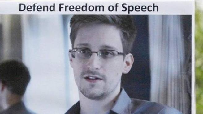 Un hombre sostiene una foto de Edward Snowden reivindicando la defensa de la libertad de expresión.