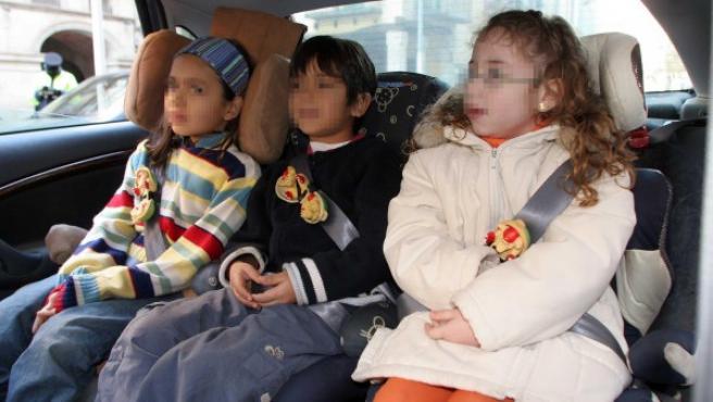 Tres niños montados en sus sillas de seguridad en un coche.