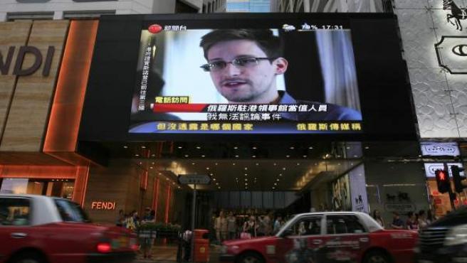 El extécnico de la CIA Edward Snowden aparece en una pantalla colocada en una calle de Hong Kong, lugar que forma parte de su odisea particular en su huida de EE UU.