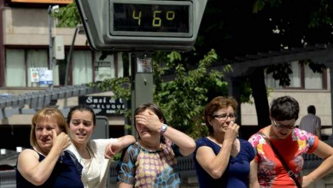 Unas mujeres sufren la ola de calor ante un termómetro de calle expuesto al sol que marca 46 grados, en el centro de la ciudad gallega de Ourense.
