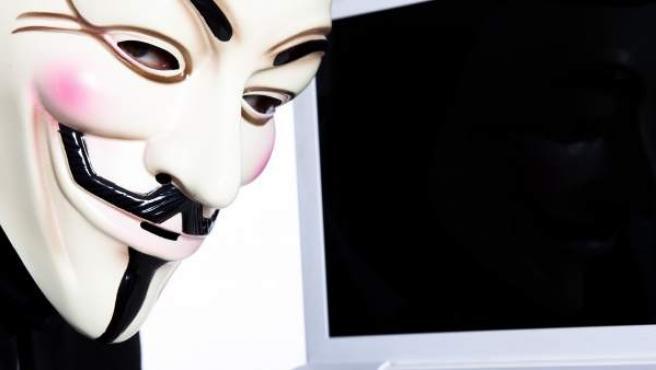Un hombre con una máscara de Guy Fawkes —adoptada como símbolo por el colectivo Anonymous— posa junto a un portátil.