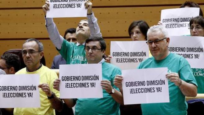 """Varios diputados de Izquierda Plural, entre los que se encuentran, Cayo Lara (d), muestran varias pancartas en las que se puede leer """"Gobierno dimisión, elecciones ya""""."""
