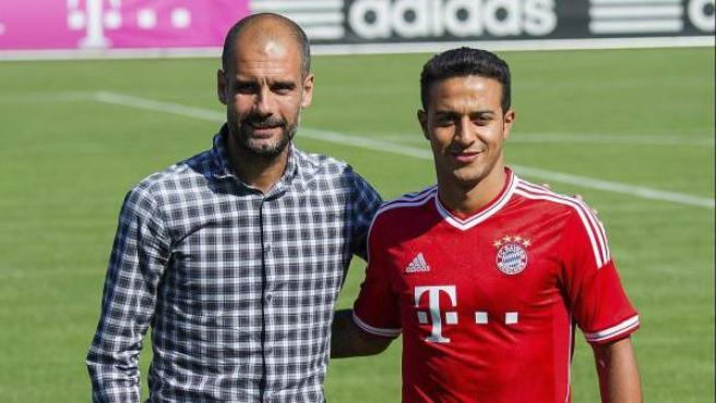 El entrenador español de Bayern Múnich, Pep Guardiola (i) posa con el centrocampista Thiago Alcántara (d) durante la presentación de éste como nuevo jugador del club alemán.