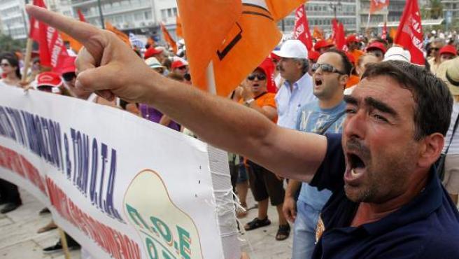 Varios empleados públicos protestan en los alrededores del Parlamento en Atenas, durante la jornada de huelga general en contra de los despidos de funcionarios previstos en el nuevo acuerdo con la troika.