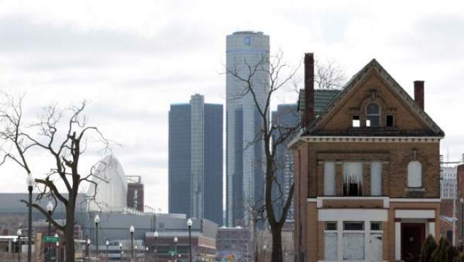 Fotografía del 3 de marzo de 2013 de una casa abandonada con el edificio de General Motros de fondo, en Detroit.