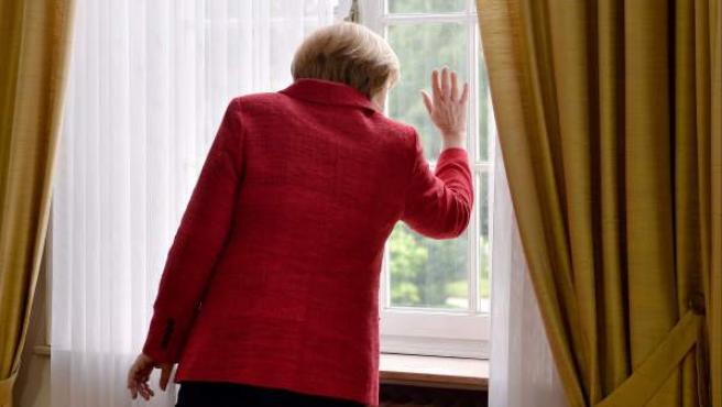 La canciller alemana, Angela Merkel, observa desde la ventana del antiguo despacho del excanciller Konrad Adenauer en Bonn.