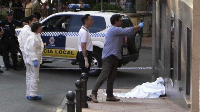 Miembros de la Policía Local y Nacional junto al cadáver (tapado con una sábana blanca) de un hombre que falleció tras recibir un disparo en la cabeza en Cuenca.