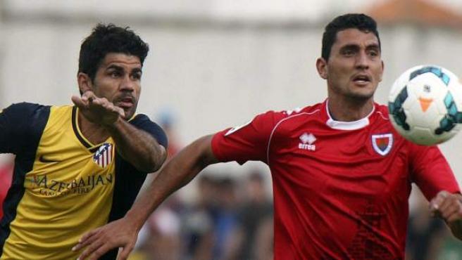 Diego Costa (izquierda) pugna por el balón con Juanma durante el amistoso de pretemporada disputado entre el Atlético de Madrid y el Numancia.