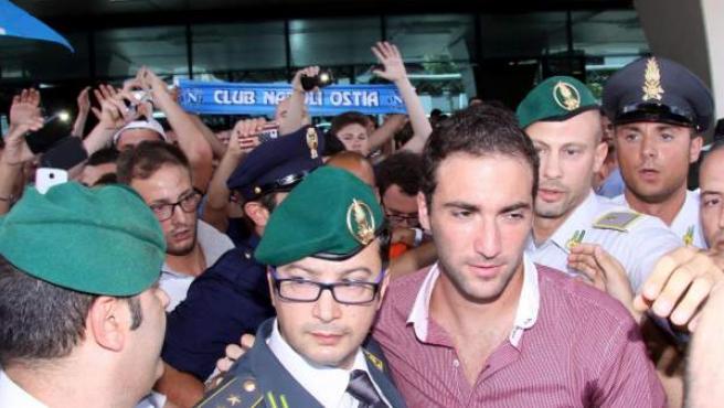 El delantero argentino Gonzalo Higuaín aterriza en el aeropuerto romano de Fiumicino, donde fue recibido por varias decenas de aficionados napolitanos.