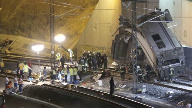 Los servicios de emergencia sanitaria junto a las vías tras el accidente del tren Alvia que cubría la ruta entre Madrid y Ferrol y que ha descarrilado esta noche cuando ya estaba muy cerca de Santiago de Compostela.