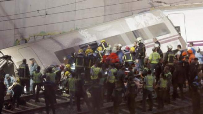 Los servicios de emergencia sanitaria atienden a los heridos en el lugar del accidente donde el tren Alvia que cubría la ruta entre Madrid y Ferrol ha descarrilado esta noche, cuando ya estaba muy cerca de Santiago de Compostela.
