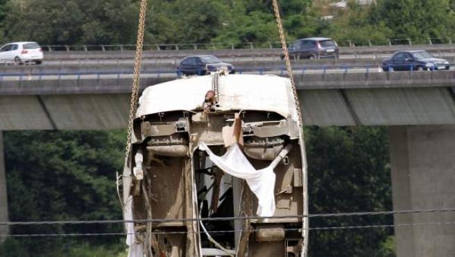 Una grúa retira uno de los vagones del tren descarrilado en Santiago de Compostela.