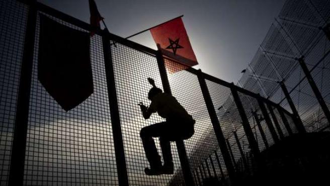 Un joven trepa por una verja junto a la valla en la frontera entre Melilla y Marruecos.