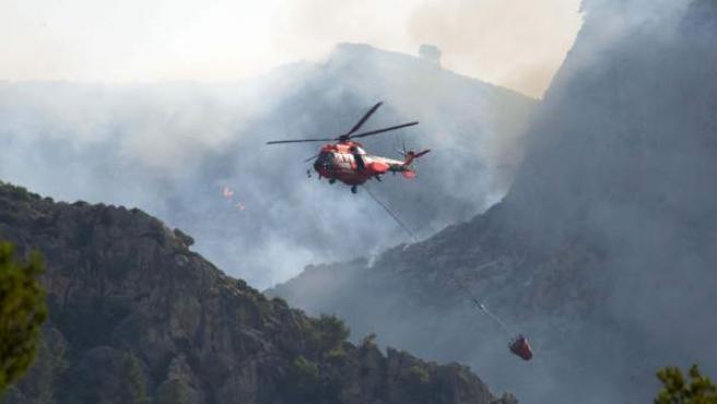 Un helicóptero trabaja en las labores de extinción del incendio que afecta a los municipios de Andratx y Estellens, en Mallorca.