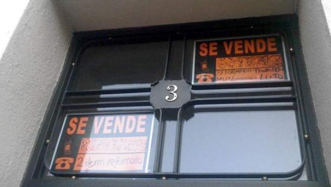 El cartel de dos pisos en venta, en la puerta de un edificio.