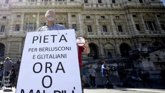 """Un hombre sujeta una pancarta que reza """"Piedad para Berlusconi y los italianos, ahora o nunca"""" frente a la sede del Tribunal Supremo en Roma (Italia)."""