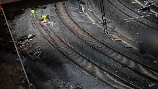 Un grupo de operarios trabaja en la curva de A Grandeira, donde descarriló el tren Alvia a pocos kilómetros de la estación de ferrocarril de Santiago de Compostela, para retirar lo que queda del convoy accidentado y el acondicionamiento de las vías.