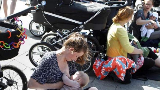 Varias mujeres dan el pecho a sus hijos durante una protesta en contra de la prohibición de dar el pecho en algunas cafeterías y lugares públicos, en la plaza del Ayuntamiento de Copenhague, Dinamarca.