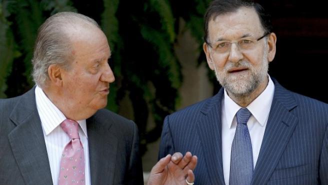 El rey Juan Carlos conversa con el presidente del Gobierno, Mariano Rajoy (d), a quien ha recibido en el único despacho del verano que celebrarán en el Palacio de Marivent.