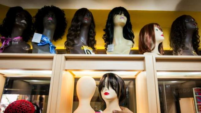 Detalle de una estantería con varias pelucas de colores en Caracas.