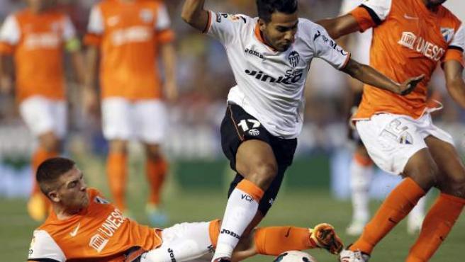 El valencianista Viera intenta llevarse el balón ante los jugadores del Málaga Antunes y Tissone.