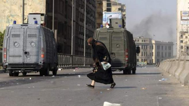 Una mujer cruza la calle junto a vehículos de las fuerzas de seguridad egipcias.