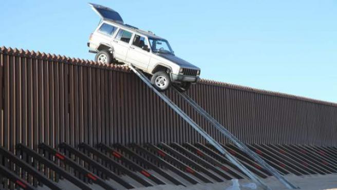 Un vehículo en lo alto de una valla fronteriza con México cerca de la localidad de Yuma, Arizona (EE UU). Dos personas trataron de entrar al país conduciendo su todoterreno por encima de la valla fronteriza de cuatro metros de altura, un intento que resultó frustrado cuando el automóvil se quedó atascado sobre la empalizada.