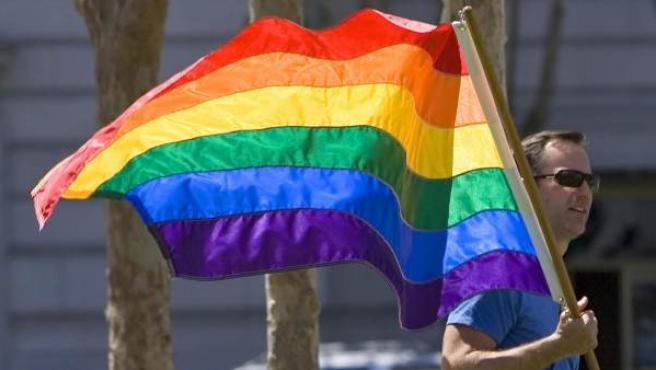 Un hombre porta una bandera arcoiris.