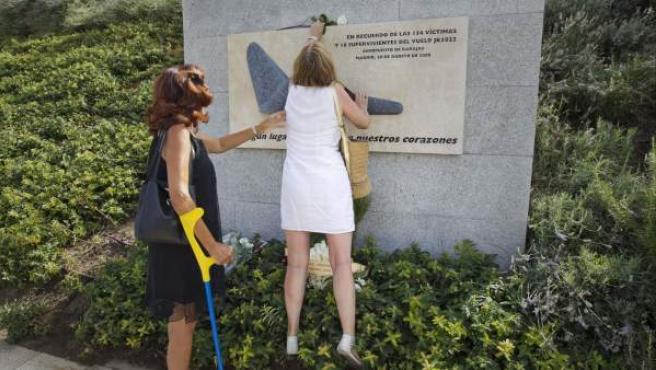 Dos componentes de la Asociación de Afectados del Vuelo JK5022 colocan una rosa blanca en el monumento a los fallecidos situado en La Rosaleda del Parque Juan Carlos I en señal de recuerdo a las 154 personas que murieron el 20 de agosto de 2008 en el accidente de un avión de la compañía Spanair en el aeropuerto de Barajas.