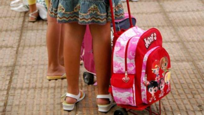 Un grupo de menores espera para entrar a su colegio.