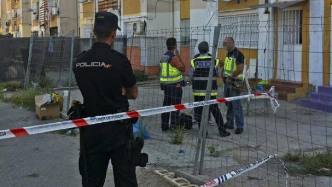 Miembros de la Policía Nacional, ante la fachada del edificio donde una niña de 7 años murió en un tiroteo en las Tres Mil Viviendas de Sevilla.