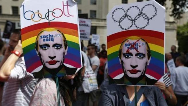 Activistas sujetan pancartas con la cara del presidente Putin maquillada en protesta por el tratamiento de los homosexuales en Rusia.