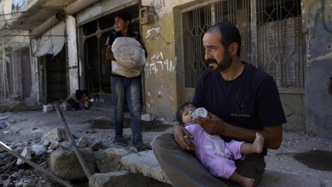 Un hombre da un biberón a su hija frente a su hogar, parcialmente destruido por la guerra en Alepo (Siria). Foto de Muhammed Muheisen