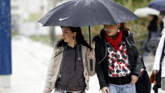 Dos chicas resguardándose de la lluvia bajo un paraguas.