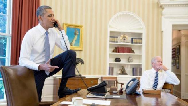 Barack Obama, en su despacho de la Casa Blanca, conversa en una postura muy informal por teléfono con Joe Biden de fondo.