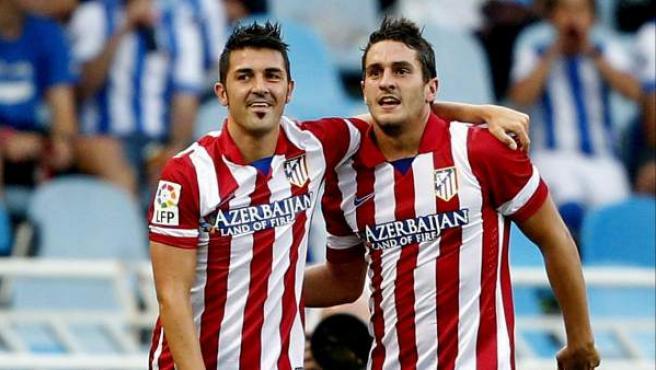 David Villa y Koke Resurrección, del Atlético de Madrid, celebran el gol del segundo en el estadio de Anoeta.