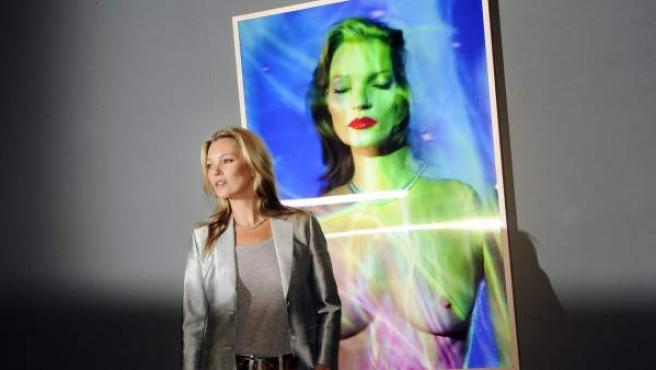 """La supermodelo británica Kate Moss posa junto a una fotografía tomada por Chris Levine titulada """"She's Light"""" durante la presentación a los medios de la subasta que celebra en Christie's."""