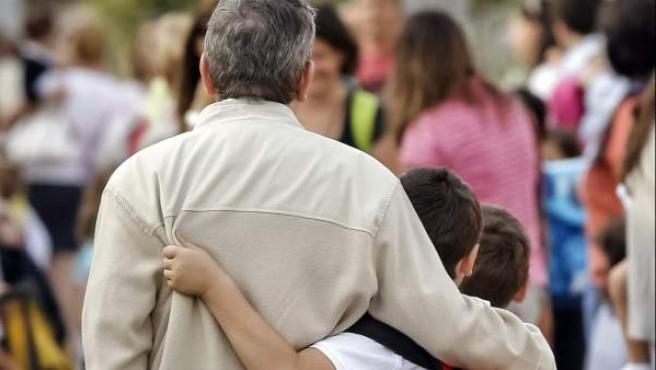 Un padre acompaña a sus dos hijos a clase al inicio del curso escolar, en el colegio Calvo Sotelo (Madrid).