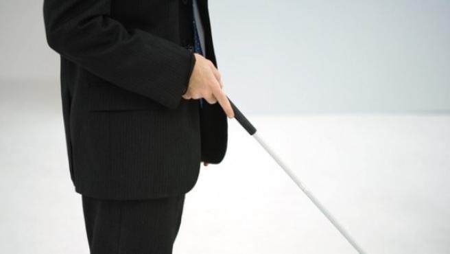 Una persona ciega camina ayudada por un bastón.