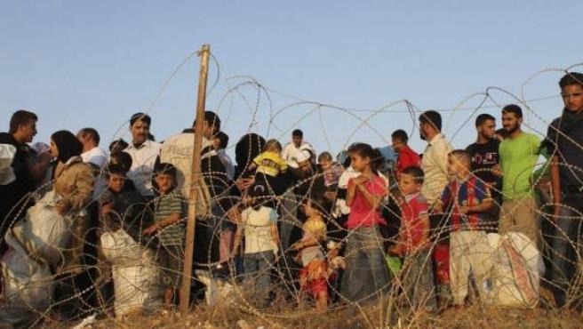 Un grupo de refugiados sirios, que huyeron de la violencia en su país, haciendo cola en la frontera siria con Turquía, en Hatay. Hasta ahora han muerto en el conflicto más de 200.000 personas y se han convertido en refugiados más de 3.000.000. En total, seis millones de desplazados.