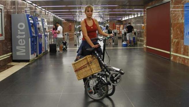 Ana Jiménez, con su bicicleta plegable en uno de los vestíbulos de la estación Méndez Álvaro, en el metro de Madrid.